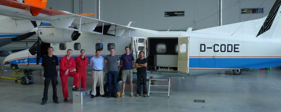 APEX team poseert bij vliegtuig